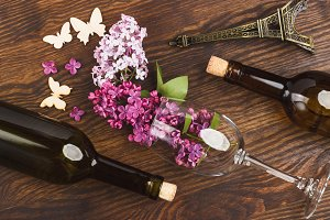 Wineglass with violet lilacs and decorations