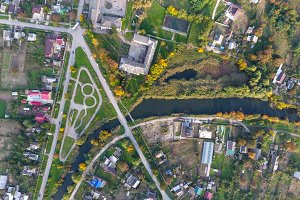 Top view of the village. One can see the roofs of the houses and gardens. Road and water in the village. Village bird's-eye view