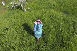 Young girl in a light green dress on the lawn with green grass. View of a man from above from a height.