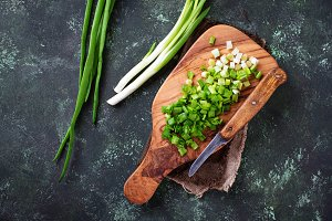 Chopped green onions on concrete background