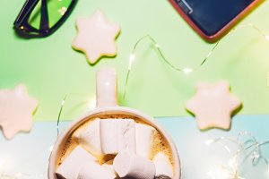 hot coffee with milk and foam. marshmallow in coffee. garlands glow. holiday. technology and glasses. cookies in the form of stars
