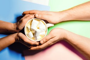 A loving couple is holding a mug with a hot drink. in coffee with foam chewing marshmallows. view from above. background of three colors. feelings of love
