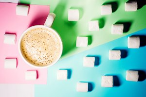 on a blue, green, pink background is marshmallow. mug with hot coffee with foam