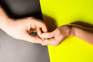 touching the hands of a pair. tenderness and love. view from above. background is yellow and black
