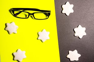 biscuit in a glaze on a black background. glasses for work. feast, feast
