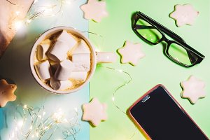 hot drink with marshmallow. cookies with icing in the form of stars. gadgets and glasses for sight