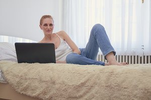 one woman, looking at camera, relaxing laying in bed. white spacious room, daylight windows behind.