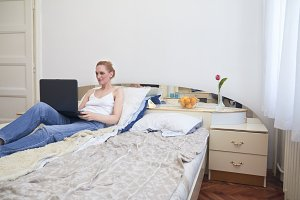 one woman, laying in bed smirking, using laptop. ordinary white room interior.