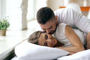 Young beautiful and loving couple wake up at the morning. Attractive man kiss and hug his wife in bed