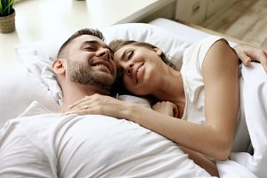 Closeup of young beautiful and loving couple talk and hug into bed while waking up in the morning.