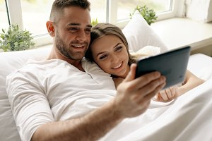 Young cute and loving couple using tablet computer and talking lying in bed in the bedroom at morning