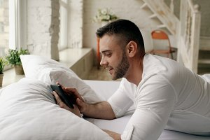 Young attractive man using tablet computer lying in bed in the morning at home