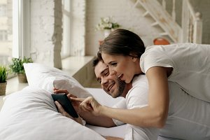 Young attractive man using tablet computer lying in bed while his girlfriend come and hug him in bedroom at the morning
