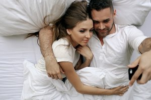 Young beautiful and loving couple having online vidoe call with smartphone camera while lying in bed at the morning