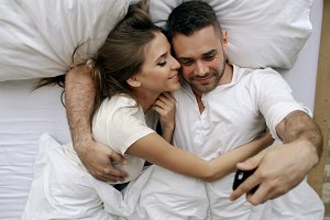 Young beautiful and loving couple take selfie picture on smartphone camera lying in bed at the morning