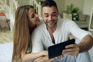 Young cute and loving couple having video chat holding tablet computer and chatting to parents sitting in bed at home
