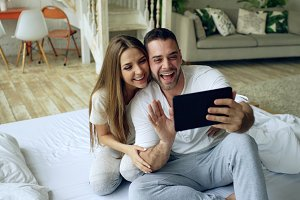Closeup of Young cute and loving couple having video chat holding smartphone and chatting to friends sitting in bed at home