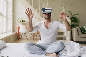 Young cheerful man wearing virtual reality headset watching 360 VR video movie sitting in the bed at home