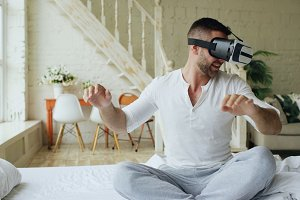 Young cheerful man wearing virtual reality headset having 360 VR video experience while sitting in bed at home