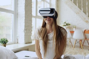Young cheerful woman wearing virtual reality headset watching 360 VR video movie sitting in the bed at home
