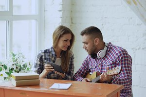 Young happy and loving couple study to play acoustic guitar using tablet computer and having fun while sitting at the table at home
