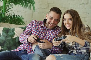 Young happy and loving couple play console game with gamepad and have fun sitting on couch in living room at home