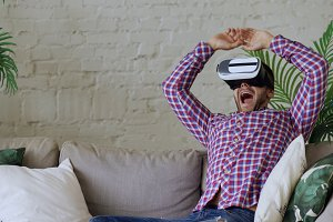Young cheerful man wearing virtual reality headset having 360 VR video experience while sitting on couch in living room at home