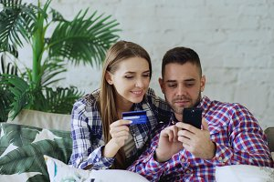 Attractive young couple with smartphone and credit card shopping on the internet sit on couch in living room at home