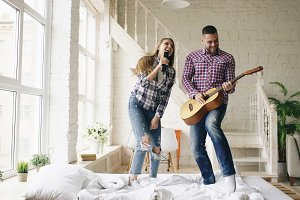 Funny happy and loving couple dance on bed singing with tv controller and playing guitar. Man and woman have fun during their holiday at home