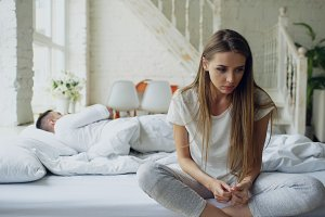 Depressed young woman sitting in bed and crying while her boylfriend lying in bed at home