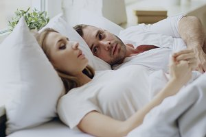 Closeup of couple with relationship problems having emotional conversation while lying in bed at home