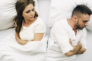 Top view of young upset couple lying in bed have problems after quarrel and angry each other at home