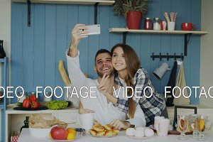 Young happy couple taking selfie portrait while having breakfast in the kitchen at home