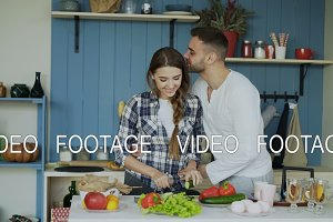 Happy young couple in the kitchen. Attractive dancing woman cooking and feeding her boyfriend in the morning