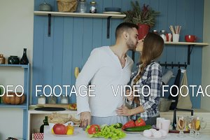 Happy young couple in the kitchen. Attractive dancing man cooking while his girfriend come and help him in the morning