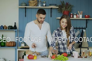 Happy young couple in the kitchen. Attractive dancing man cooking while his girfriend help him in the morning