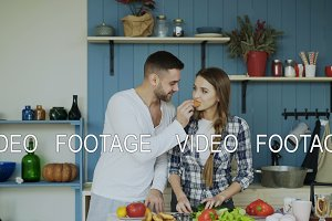 Happy young couple in the kitchen. Attractive dancing man feeding his girlfriend while she is cooking in the morning