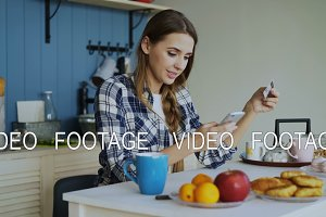Smiling woman doing online shopping using smartphone and credit card while have breakfast in the kitchen at home