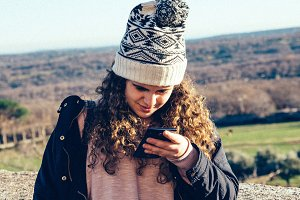 Teenage girl in knit hat texting with cell phone