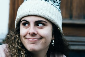 Smiling teenage girl with long and curly hair wearing knit hat