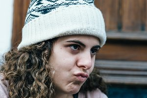Teenage girl with long and curly hair wearing a knit hat