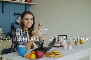 Cheerful smiling woamn talking online video chat using smartphone in the kitchen at home