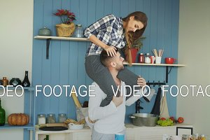 Happy young couple having fun in kitchen at home. Girl is sitting on boyfriend's neck