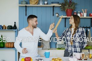 Happy couple having fun in the kitchen fighting with ladle and rolling-pin while cooking breakfast at home