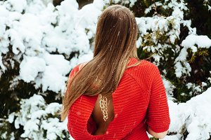 Girl in a sweater in a snowy park in