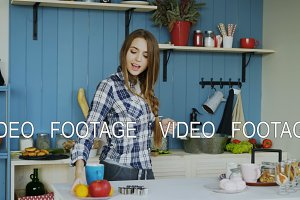 Cheerful young funny woman dancing and singing while cooking breakfast at home