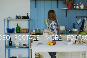 Cheerful young funny woman dancing and singing set the table for breakfast in the kitchen at home