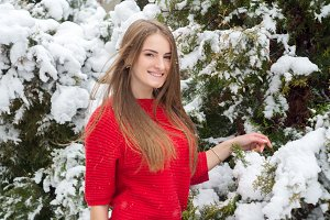 Girl in a sweater in a snowy park in winter.