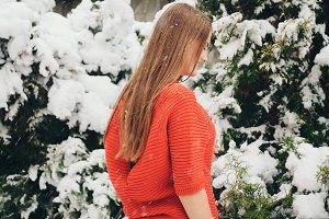 Beautiful young girl model in winter in a parked park. in a red sweater.