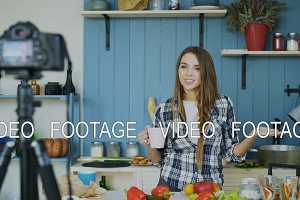 Young attractive woman recording video food blog about cooking on dslr camera in kitchen